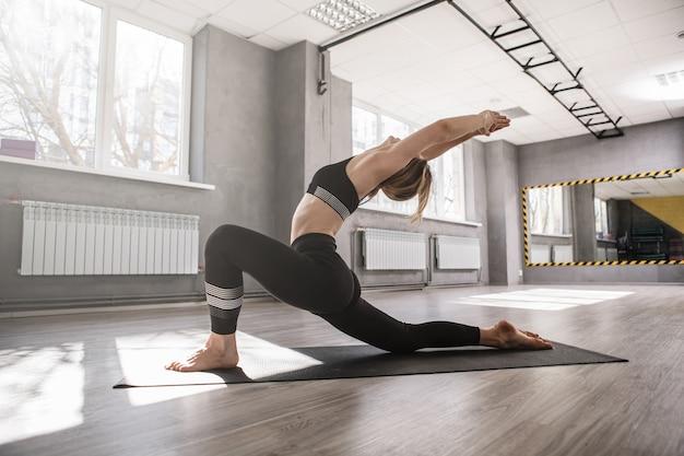 ヨガスタジオでワークアウトし、体を伸ばす若い柔軟なフィットの女性