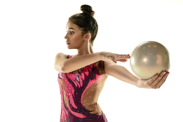 白いスタジオの背景に分離された柔軟な少女。器具を使って練習する新体操アーティストとしての 10 代の女性モデル。柔軟性、バランスのためのエクササイズ。グレース・イン・モーション、スポーツ。