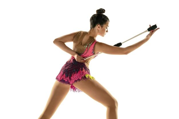 Молодая гибкая девушка, изолированные на белом фоне студии. девушка-модель-подросток как артистка художественной гимнастики занимается с оборудованием. упражнения на гибкость, баланс. изящество в движении, спорте.