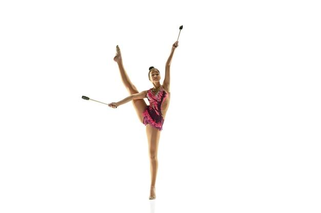 白い壁に隔離された若い柔軟な女の子。装備を練習する新体操アーティストとしての10代の女性モデル。柔軟性、バランスのためのエクササイズ。動きのある恵み、スポーツ。