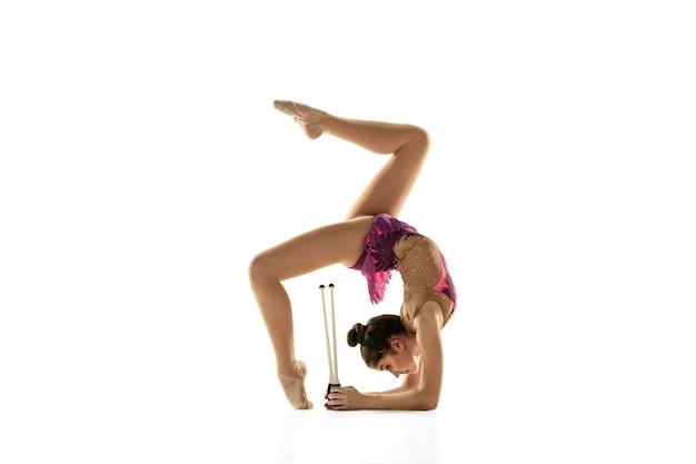 Молодая гибкая девушка изолированная на белой стене. девушка-модель в качестве артистки художественной гимнастики занимается с оборудованием. упражнения на гибкость, баланс. изящество в движении, спорте.