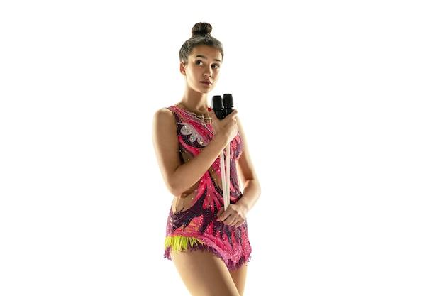 Giovane ragazza flessibile isolata su sfondo bianco. modello femminile adolescente come artista di ginnastica ritmica che pratica con attrezzature.