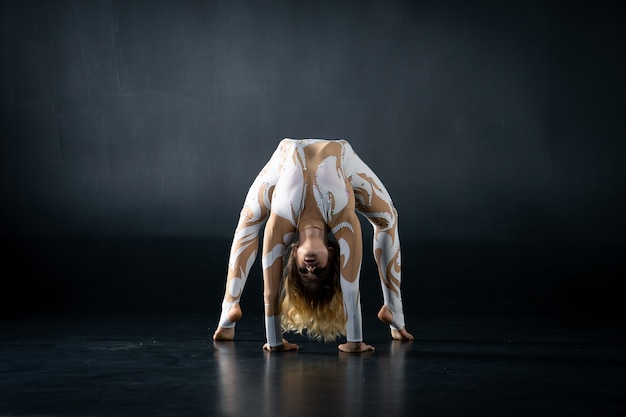 A young flexible girl performs the acrobatic elements on the floor.