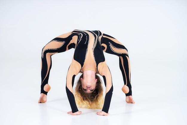 A young flexible girl performs the acrobatic elements on the floor
