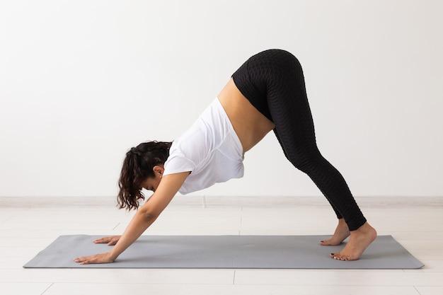敷物の上で体操をしている若い柔軟な妊婦