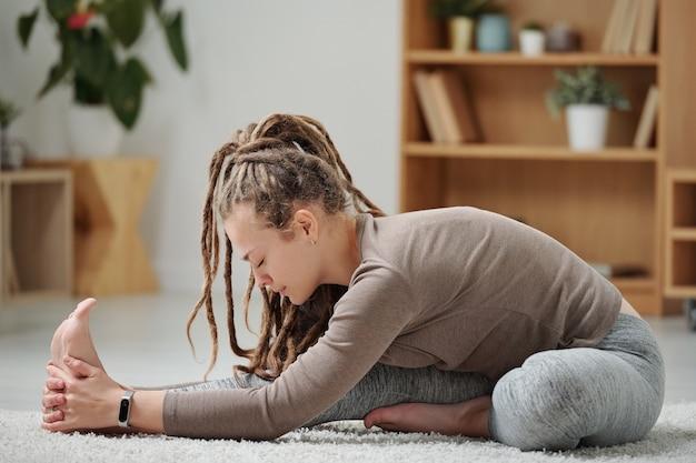 Молодая гибкая женщина в спортивной одежде сидит на полу и вытягивает вперед одну ногу, наклоняясь над ней