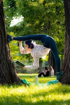 Молодая гибкая женщина читает книгу о концепции изучения и обучения пикника