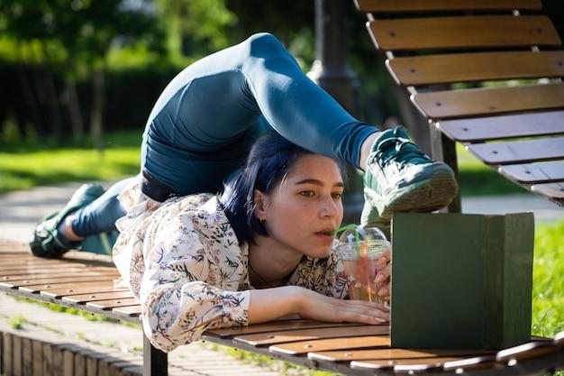 벤치에서 책을 읽는 유연한 젊은 여성이 등을 굽혀 개성 창의성과 교육을...