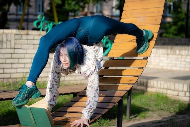 Молодая гибкая женщина, читающая книгу на скамейке, сгибая спину. концепция индивидуальности, творчества и образования. фото высокого качества