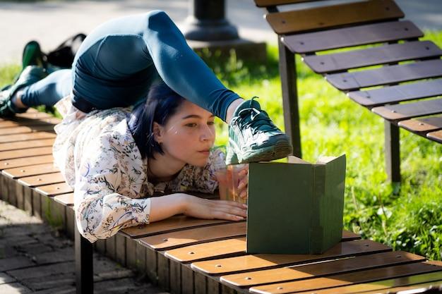 Молодая гибкая женщина, читающая книгу на скамейке, сгибая спину, концепция здорового образа жизни йоги