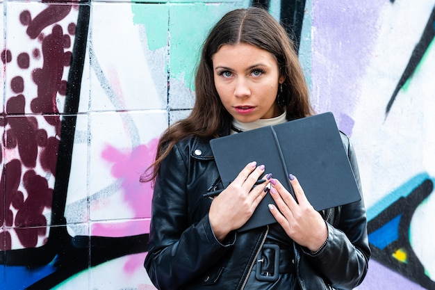A young, flirtatious female with a black bow in her hands leaning against a wall sprayed with graffiti