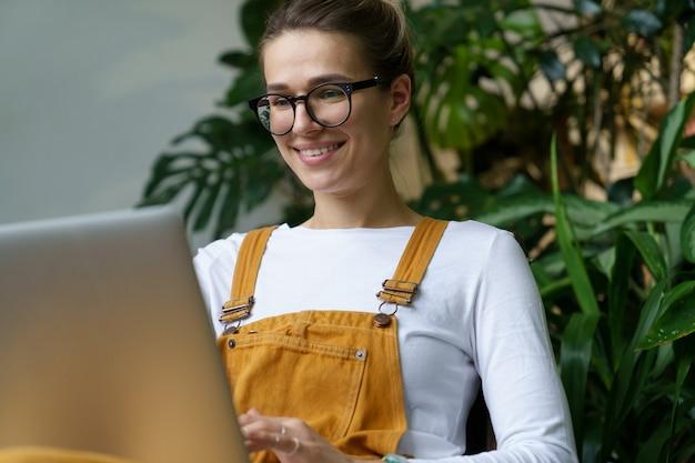 어린 꽃집 소녀는 온실에서 일한 후 노트북을 사용하여 실내 정원 가꾸기에 대한 비디오 자습서를 봅니다.