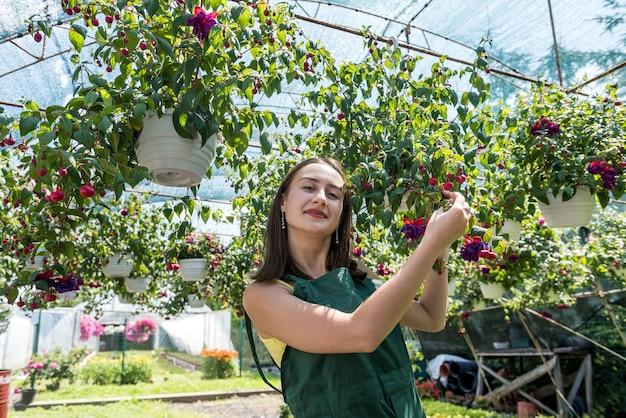 温室の花の間に均一に立っている若い花屋の女の子。春 Premium写真