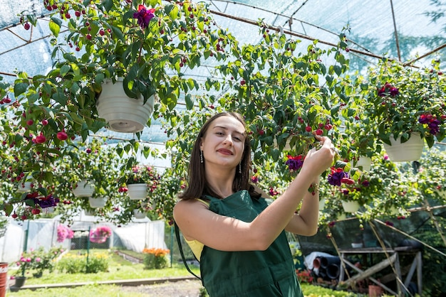 Young  florist girl with uniform standing between flowers  in greenhouse. springtime