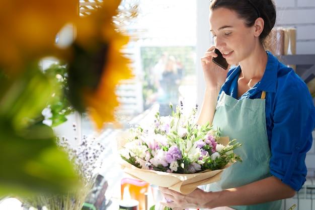 Молодой флорист говорит по телефону
