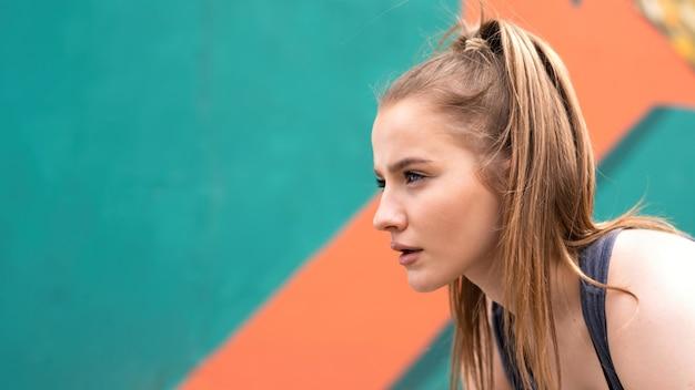 ランニングを始める準備をしている屋外トレーニングで若い焦点を当てた金髪の女性、色とりどりの背景
