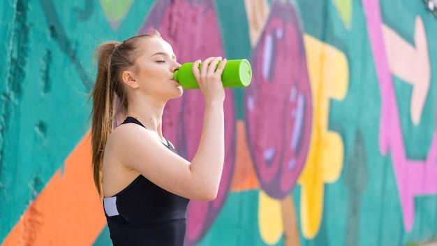 야외 훈련에서 스포츠 음료수에 젊은 집중된 금발의 여자, 여러 가지 빛깔의 배경