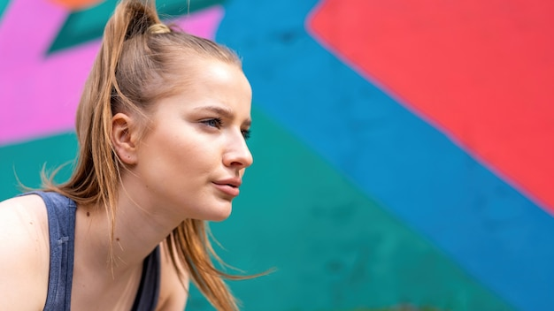Young focused blonde woman at outdoors training preparing to start running, multicolored background