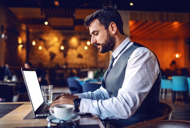 Young focused caucasian bearded businessman in suit sitting in cafe and finishing his report.