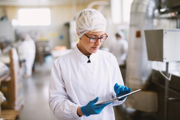젊은 여성 식품 공장에서 생산 라인의 생산성을 확인하는 멸균 옷에 집중.