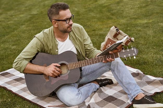 Молодой целеустремленный мужчина-музыкант в очках читает ноты и практикует акустическую гитару