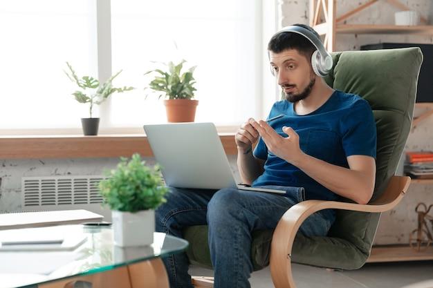 Молодой целеустремленный мужчина учится дома во время онлайн-курсов или самостоятельно получает бесплатную информацию