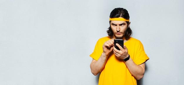 灰色の背景にスマートフォンを使用して若い焦点を当てた男。黄色いシャツとバンドを着ています。コピースペース付きのパノラマバナービュー。