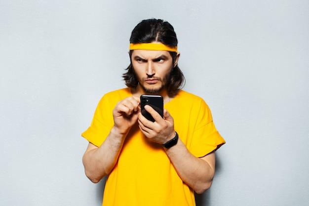 灰色の背景にスマートフォンを使用して若い焦点を当てた男。黄色いシャツとバンドを着ています。