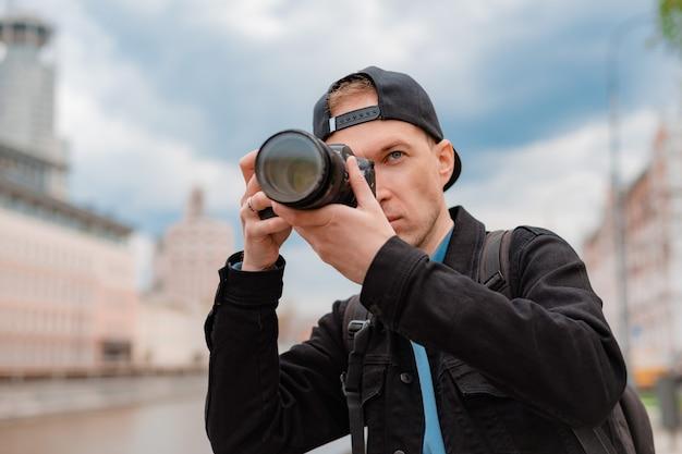 젊은 밀레니얼 남성 사진가는 야외에서 전문 카메라로 사진을 찍으려고 합니다.