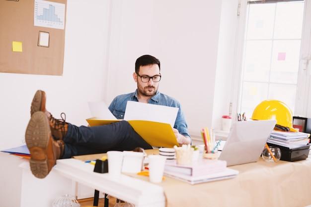 若者は、フォルダーからのレポートを見て、オフィスの机の上の足で現代のビジネスマン起業家に焦点を当てました。