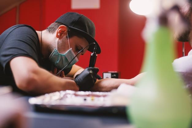 Молодой целеустремленный художник-татуировщик тщательно накрашивает руки клиентов в своем магазине.
