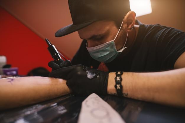 若い集中タトゥーアーティストが彼の店で顧客の腕に慎重にインクを塗っています。