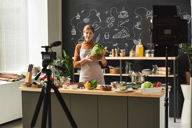 野菜を手に持った若い食品ブロガーが、ブログを運営しているカメラでビデオを録画しています