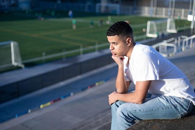 Молодой футбольный фанат скучает, сидя на трибунах стадиона