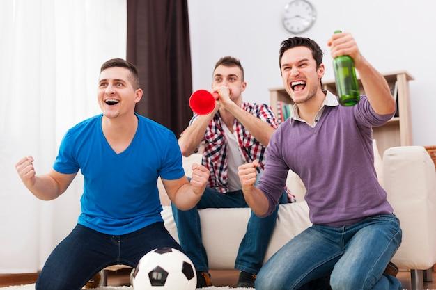 若いサッカーファンはテレビでサッカーをサポートしました