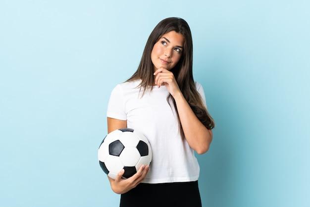 Бразильская девушка молодой футболист изолирована на синем и смотрит вверх