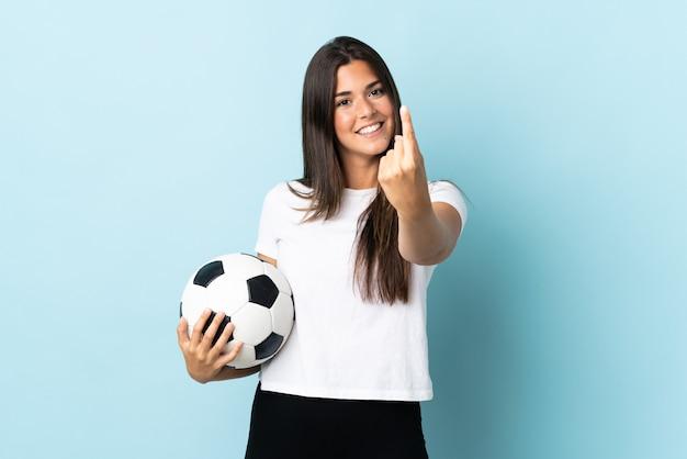 来るジェスチャーをしている青い背景で隔離の若いサッカー選手ブラジルの女の子