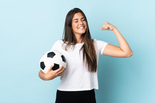 Бразильская девушка молодой футболист, изолированные на синем фоне, делает сильный жест