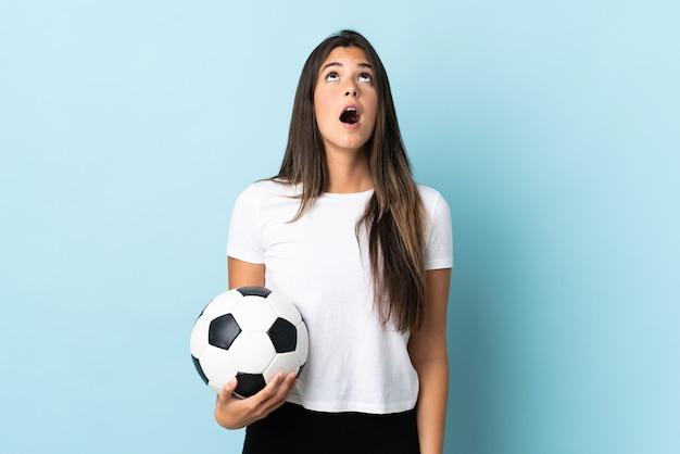見上げると驚いた表情で青い背景に分離された若いサッカー選手ブラジルの女の子