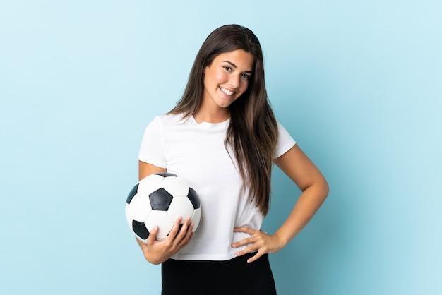 腰と笑顔で腕でポーズをとって青い背景で隔離の若いサッカー選手ブラジルの女の子