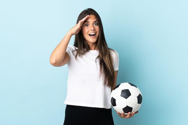Бразильская девушка молодой футболист изолирована на синем фоне с выражением удивления