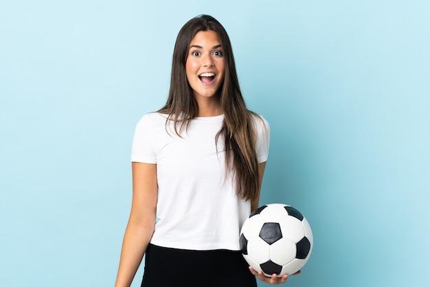 驚きの表情で青い背景に分離された若いサッカー選手ブラジルの女の子