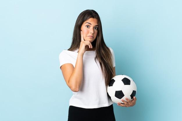 Бразильская девушка молодой футболист изолирована на синем, думая об идее