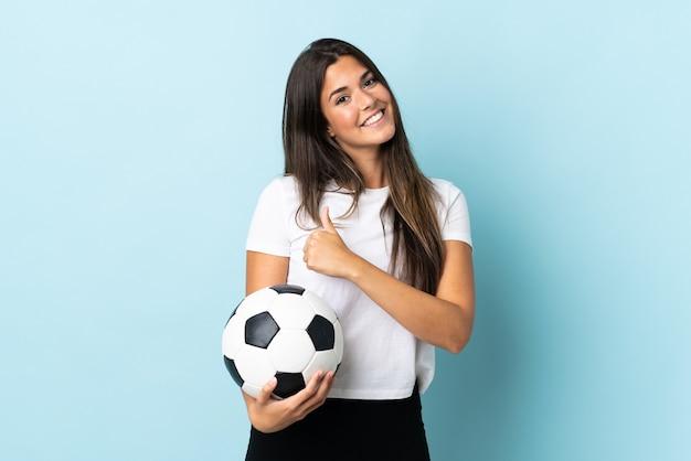 Бразильская девушка молодой футболист изолирована на синей стене, показывая большой палец вверх