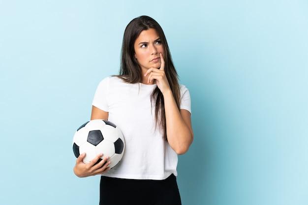 Бразильская девушка молодой футболист изолирована на синей стене, сомневаясь, глядя вверх