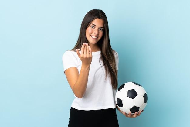 Бразильская девушка молодой футболист, изолированные на синей стене, приглашая прийти с рукой. счастлив что ты пришел