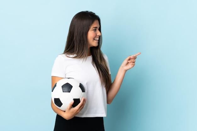 Бразильская девушка молодой футболист изолирована на синей стене, указывая пальцем в сторону и представляет продукт