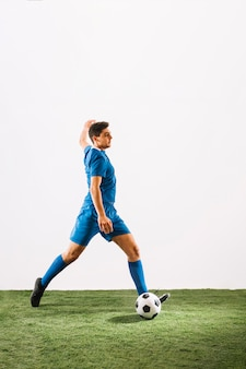Young football player crossing ball
