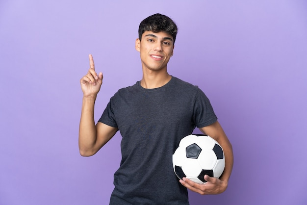 Young football player man over isolated purple background showing and lifting a finger in sign of the best