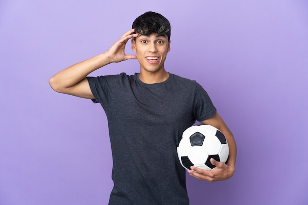 Young football player man over isolated purple background with surprise expression